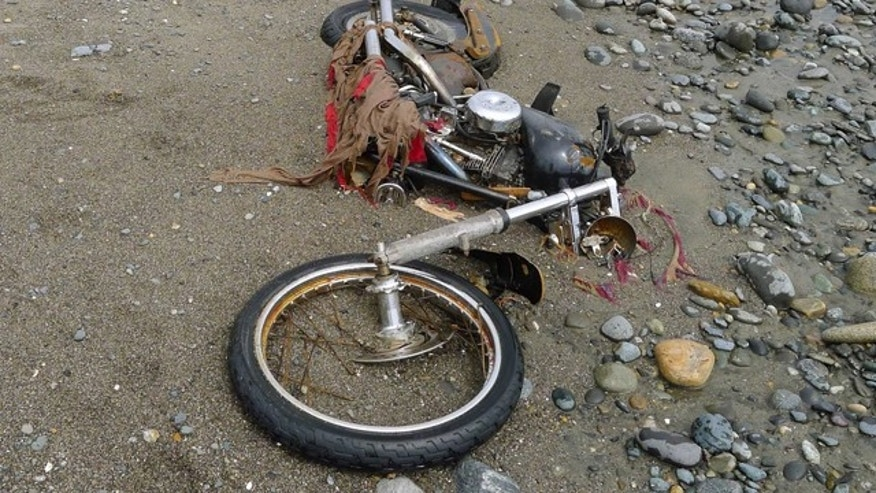 May 2, 2012: A Japanese motorbike lies on a beach in Graham Island, western Canada.