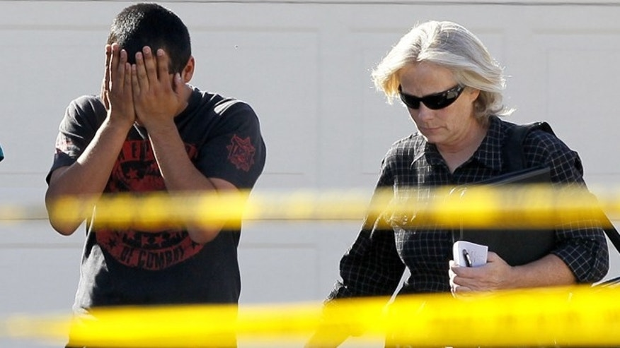 A police officer walks with a man who said he had a child inside of the home where five people were shot Wednesday, May 2, 2012 in Gilbert, Ariz.   Police have identified one of the five people killed in a shooting in a Phoenix suburb as a former Marine with ties to new-Nazi and Minutemen groups.