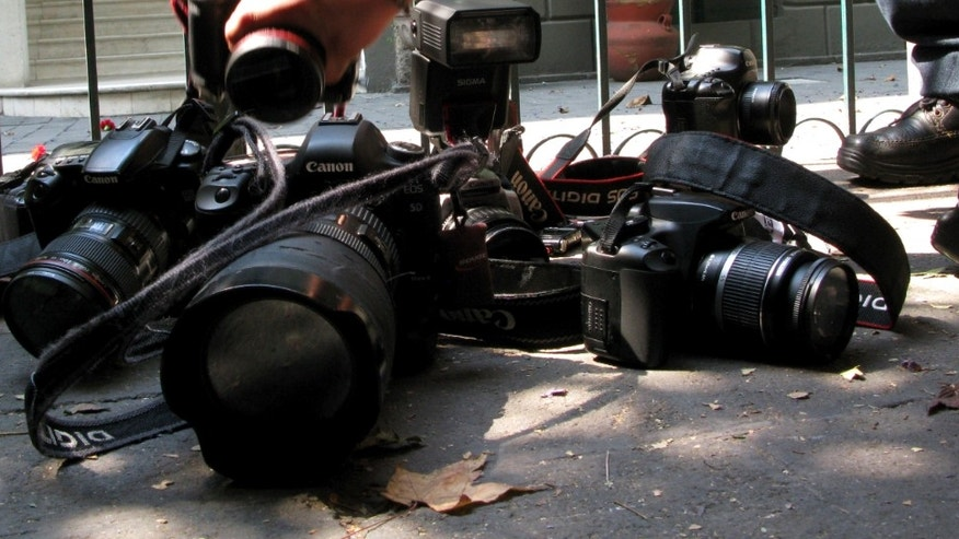 Photojournalists place their cameras on the floor during a demonstration condemning the alleged murder of fellow journalist Regina Martinez in Mexico City, Sunday April 29, 2012. The Mexican government's human rights commission said Sunday that it will investigate the apparent slaying of a correspondent for Proceso newsmagazine who often wrote about drug trafficking. Police found the body of Martinez on Saturday inside the bathroom of her home in the Veracruz state capital, Xalapa.  (AP Photo/Marco Ugarte)
