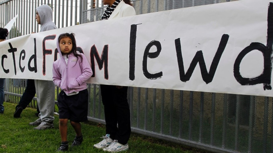 Ivis Urbina, right, with her granddaughter Alexa Agillon, 6, protest with others outside Miramonte Elementary school in Los Angeles Monday, Feb. 6, 2012. About three dozen parents and supporters staged a protest at the Los Angeles-area school rocked by allegations of lewd conduct crimes by two teachers against children. They demanded greater communication with education officials and the placement of cameras in classrooms and hallways at Miramonte Elementary School. (AP Photo/Damian Dovarganes)