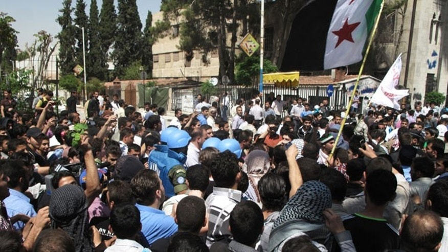 In this Monday, April 23, 2012 photo, Syrian protestors gather around U.N. observers during their visit in Douma near the capital of Damascus, Syria.