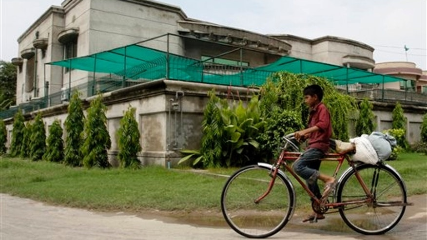 Aug. 15: A boy rides a bike past the house of kidnapped American development expert Warren Weinstein in Lahore, Pakistan.