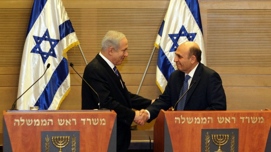 May 8, 2012: Israel's Prime Minister Benjamin Netanyahu, left, and Kadima party leader Shaul Mofaz shake hands before holding a joint press conference announcing the new coalition government, in Jerusalem.