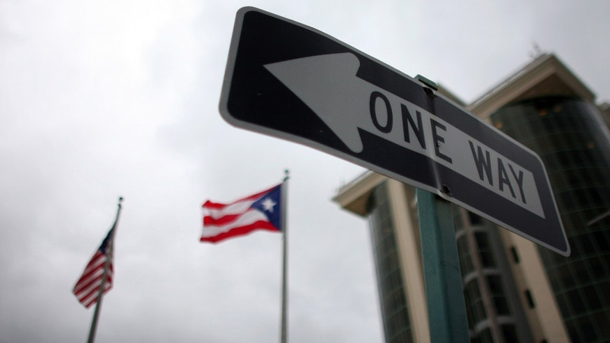 In this May 4, 2012 photo, the flags of Puerto Rico and the U.S. wave behind an English one-way traffic sign in Guaynabo, Puerto Rico, one of only a few places in Puerto Rico with street signs in English. (AP Photo/Ricardo Arduengo)