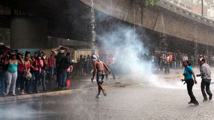 Mary 8, 2012: Relatives of inmates, protesting against measures taken by authorities to control a riot at the La Planta prison, run away from tear gas canisters fired by National Guard soldiers during clashes outside the prison in Caracas, Venezuela.