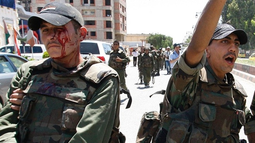 May 9, 2012: An injured Syrian army soldier, left, walks next to his comrade after a roadside bomb hit their military truck, in Daraa city, southern Syria.