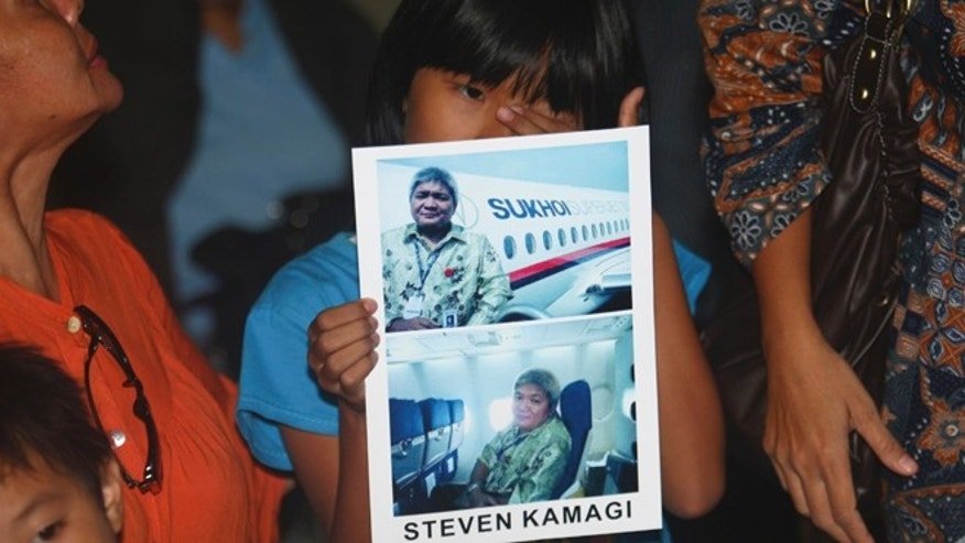 May 10, 2012: Tasya Kamagi, 10, holds the pictures of his father Steven that were taken when he boarded a Russian-made Sukhoi Superjet-100 that crashed on a mountainous area in West Java, at Halim Perdanakusuma Airport in Jakarta, Indonesia.