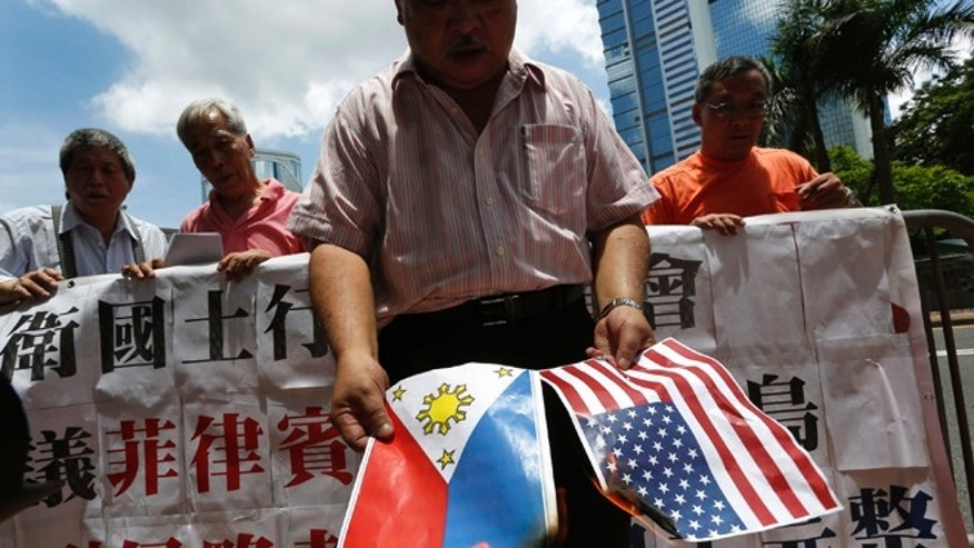 May 10, 2012: A protesters burns a Philippine flag and a U.S. flag during a protest outside the Philippines Consulate in Hong Kong.