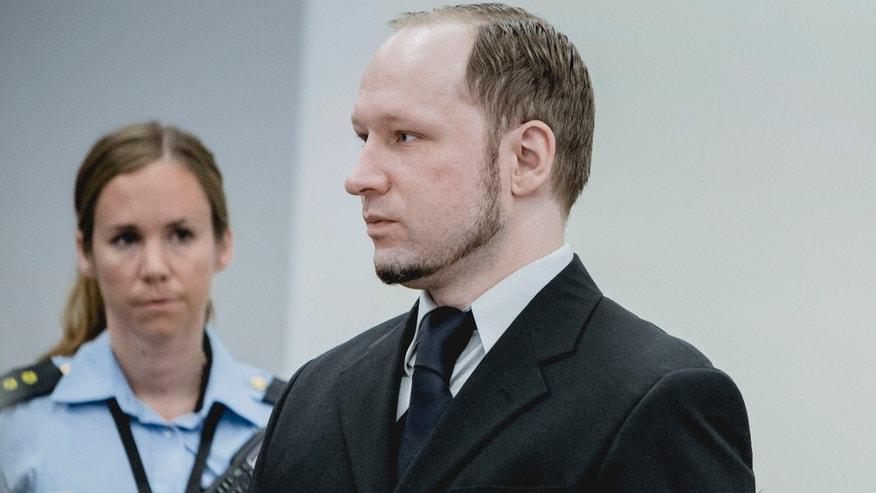May 10, 2012: Anders Behring Breivik, who has admitted to the July 22, 2011 massacre and a bombing in Oslo that killed eight people earlier that day, stands with a police woman in court in Oslo.