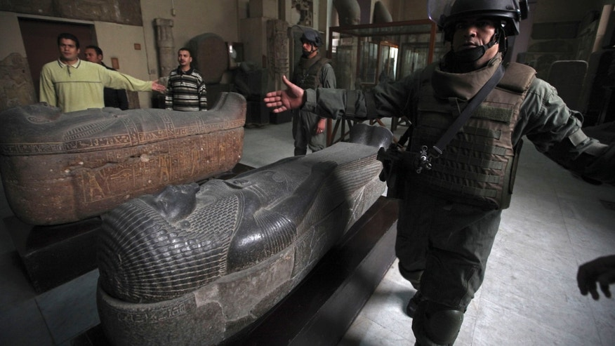 In this file photo, Army special forces gesture as they escort journalists during a tour for the media in the Egyptian Museum in Cairo. Taking advantage of Egypt's political upheaval, thieves have gone on a treasure hunt with a spree of illegal digging, preying on the country's ancient pharaonic heritage.