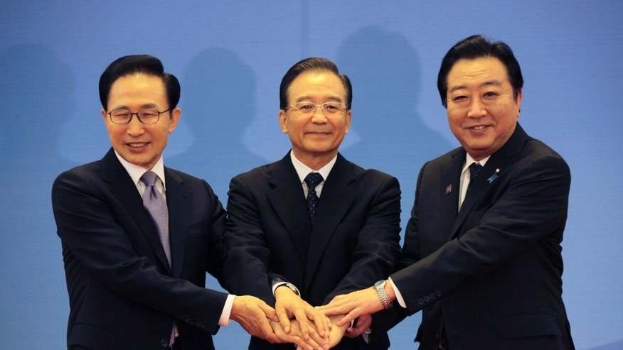 May 13, 2012: South Korea's President Lee Myung-bak, left, China's Premier Wen Jiabao, center, and Japan's Prime Minister Yoshihiko Noda hold their hands together as they pose for photographs ahead of the fifth trilateral summit among the three nations in Beijing.