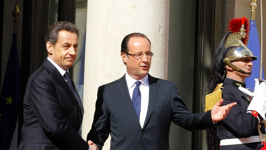 May 15, 2012: French President-elect Francois Hollande, right, shakes hands with outgoing President Nicolas Sarkozy.