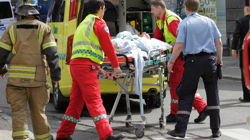May 15, 2012: A man who set fire to himself outside the courthouse in Oslo where the trial of Anders Behring Breivik is taking place, is taken into an ambulance.