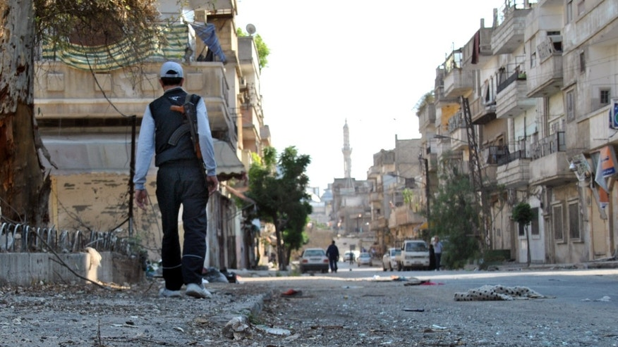 May 15, 2012: In this photo, a Syrian rebel walks in Khaldiyeh neighborhood in Homs province, central Syria.