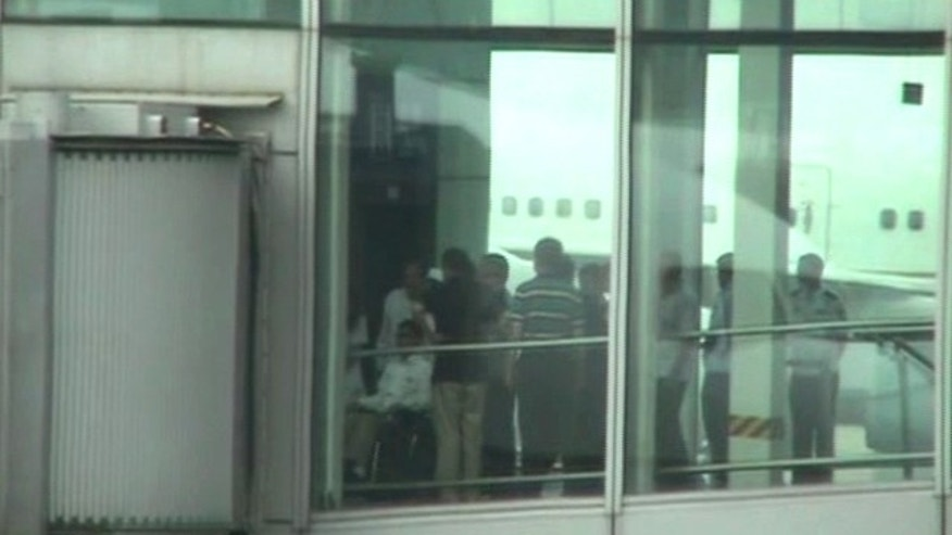 May 19, 2012: Blind Chinese activist Chen Guangcheng, left, pushed in a wheelchair from an elevator to a sky bridge that is connected to a plane at Beijing International airport.