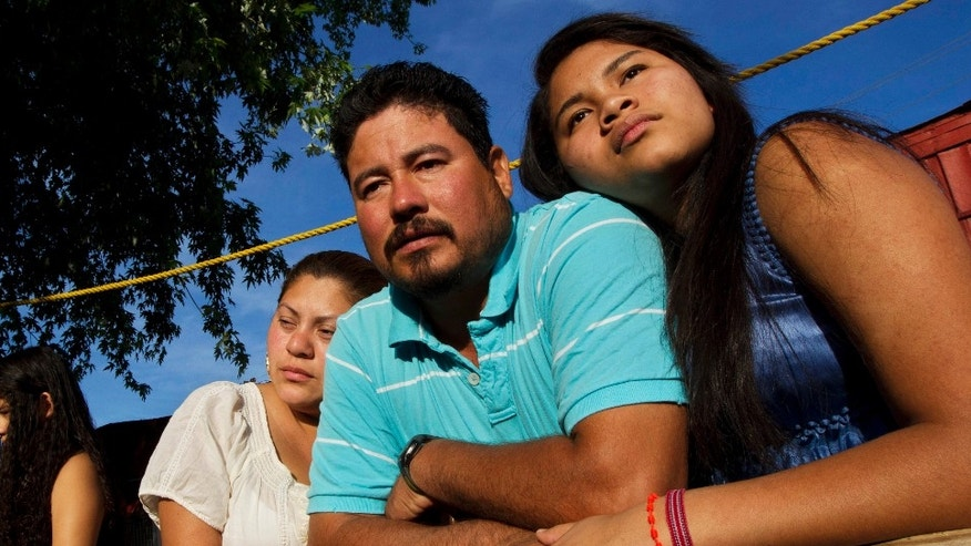 In this Thursday, April 13, 2012 photo, Diane Martell, 17, right, leans on her parents Maurcio and Guadalupe on the porch of their home in Bessemer, Ala. (AP Photo/Dave Martin)