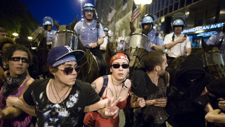 May 19, 2012: Anti-NATO protestors form a barricade in front of mounted police officers during a march in Chicago.