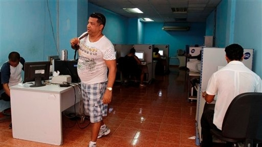 In this May 9, 2012 photo, a man leaves a state-run computer center in Havana, Cuba. Cuban officials welcomed the arrival of an undersea fiber-optic cable linking the country to Venezuela, which was supposed to boost web capacity 3,000-fold. Even a retired Fidel Castro had hailed the dawn of a new cyber-age on the island. More than a year later, the government barely speaks of the cable anymore and Cuba's internet connection is still the slowest in the hemisphere. (AP Photo/Franklin Reyes)