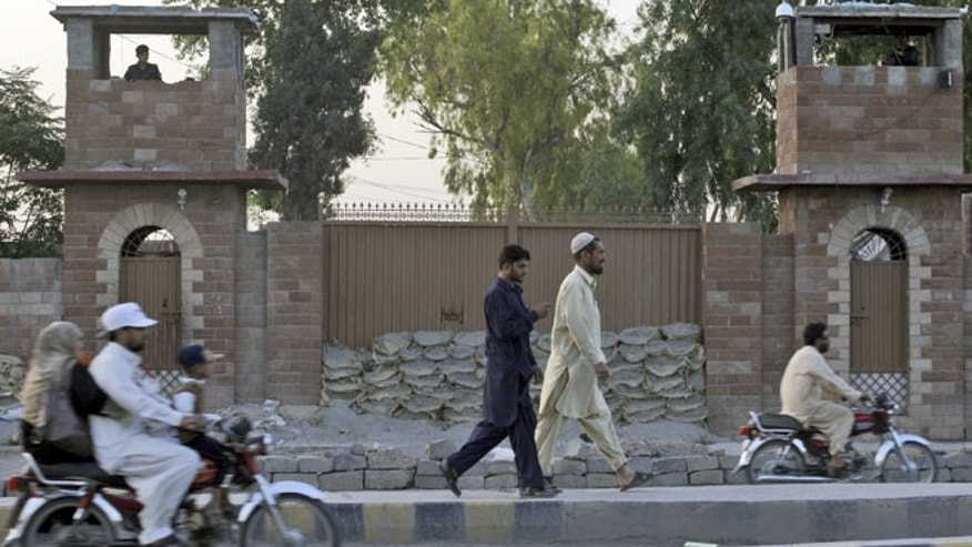 May 23, 2012: Pakistani men walk by the Central Jail in Peshawar, Pakistan.