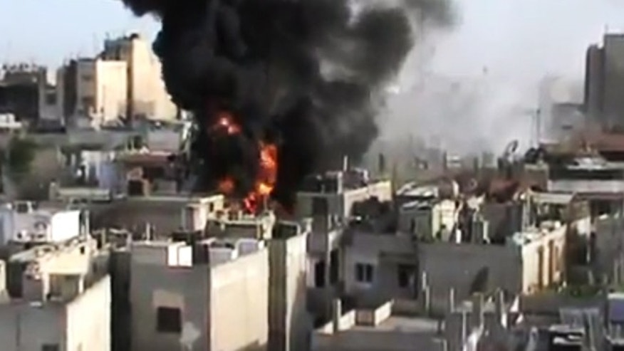 In this image made from amateur video released by the Shaam News Network and accessed Wednesday, May 23, 2012, purports to show a building on fire from shelling in Homs province, Syria.