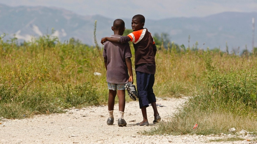 May 17, 2012: In this photo, youths walk together toward a soccer field in the Cite Soleil shantytown where a stadium may be built in Port-au-Prince, Haiti.