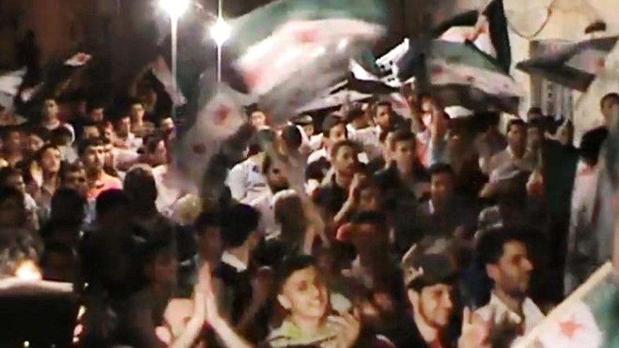This image made from amateur video and released by the Syria media center Tuesday, May 1, 2012, purports to show Syrians chanting slogans during a demonstration in Aleppo, Syria.
