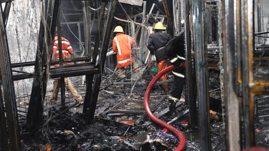 May 28, 2012: Kenyan firefighters work in shop after an explosion on a busy street in downtown Nairobi, Kenya.