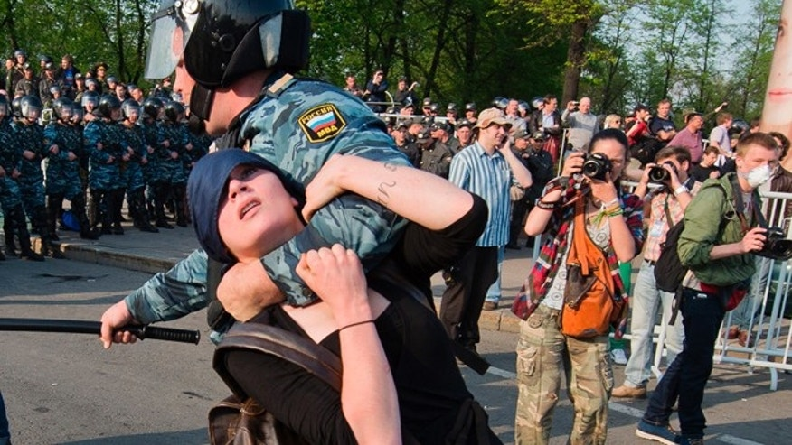 May 6, 2012: a Russian police officer detains 18-year old opposition protester Alexandra Dukhanina during an opposition rally in Moscow. Dukhanina was placed under house arrest on charges of assailing police by a court in Moscow on Tuesday, May 29, 2012.