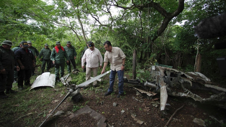 May 31, 2012: Venezuela's Justice Minister Tareck El Aissamiin, right, checks the remains of a plane used by drug traffickers during a military operation to destroy a clandestine airstrip used by drug traffickers near the border with Colombia in Riecito, Venezuela.
