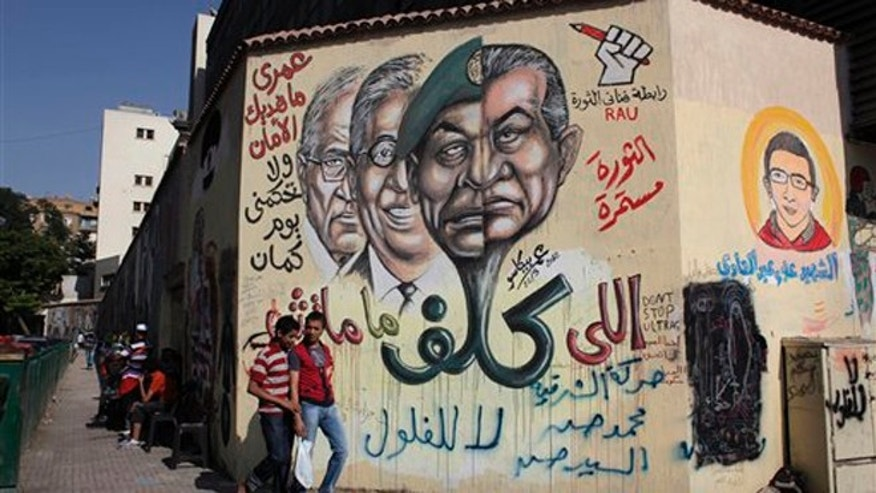 """May 31, 2012: Two Egyptian youths pass by a wall with graffiti depicting, from right, ousted Hosni Mubarak, military ruler Hussein Tantawi, presidential disqualified presidential candidate Amr Moussa and presidential candidate Ahmed Shafiq and Arabic that reads, """"I will never give you peace and you will not rule me another day, the revolution continues,"""" at Tahrir Square, Cairo, Egypt."""