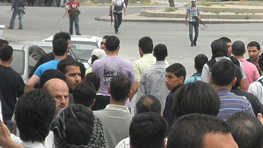 April 30, 2012: In this file photo, Syrian security forces, background, hold their machine guns and surround anti-Syrian regime mourners, foreground,  during the funeral procession of the activist Nour al-Zahraa, 23, who was shot by the Syrian security forces on Sunday, in Kfar Suseh area, in Damascus, Syria.