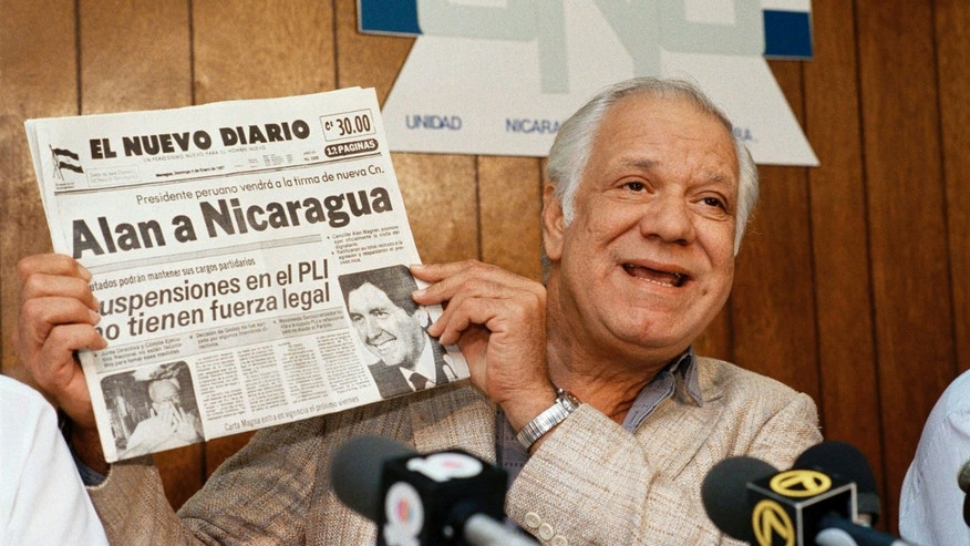 Contra leader Adolfo Calero holds a copy of Nicaraguan newspaper El Nuevo Diario during a news conference in Miami on Jan. 7, 1987. (AP Photo/Doug Jennings, File)