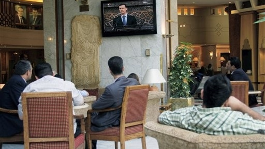June 3, 2012: People watch Syrian president Bashar Assad deliver a live speech in Damascus, Syria.