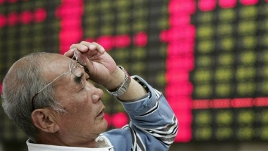 June 4, 2012: An investor looks at the stock price monitor at a private securities company in Shanghai, China.