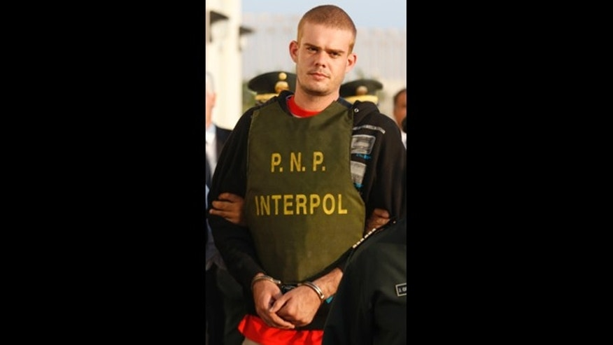 Joran Van der Sloot, top, is escorted by police officers outside a Peruvian police station, near the border with Chile in Tacna, Peru.