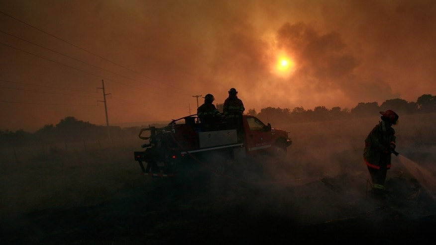GRAFORD, TX - APRIL 19:  Volunteer firefighters battle a running wildfire on April 19, 2011 in Graford, Texas. Dozens of area homes have been destroyed in the wildfires that have been fueled by dry conditions, high winds, and low humidity.  (Photo by Tom Pennington/Getty Images)