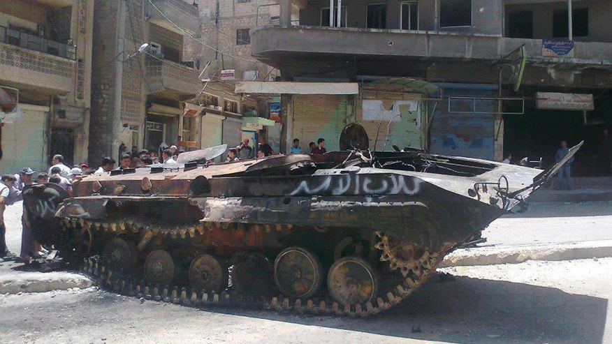 "June 4, 2012: In this citizen journalism image provided by Edlib News Network ENN, anti-Syrian regime citizens look at a Syrian military tank with Arabic that reads, ""Assads' dogs,"" that was damaged during  clashes between rebels and Syrian government forces, at the northern town of Ariha, in Idlib province."