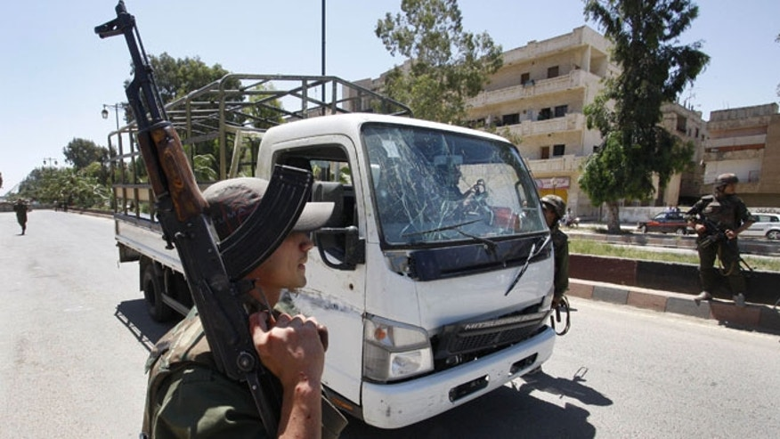 May 9, 2012: A Syrian army soldier secures the scene as he stands next to a military truck which was attacked by a roadside bomb, in Daraa city, southern Syria.