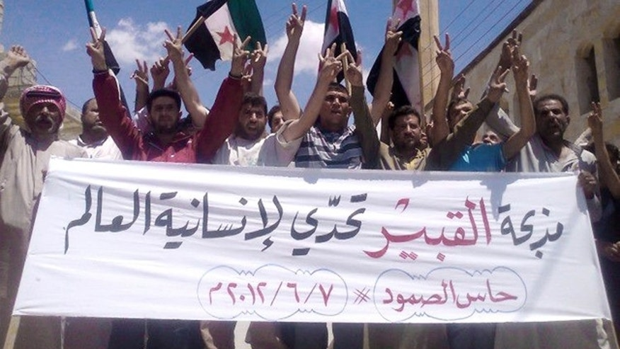 "June 7, 2012: In this citizen journalism image provided by Edlib News Network ENN, anti-Syrian regime protesters chant slogans and hold a banner in Arabic that reads, ""Al-Qubair massacre challenges the world's humanity,""during a protest against the massacre of Mazraat al-Qubair, in the northern village of Hass, in Idlib province, Syria."