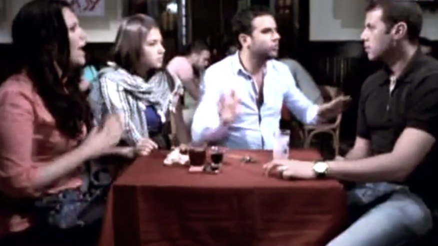 June 10, 2012: This image made from video released by the Egyptian State TV shows an actor portraying a foreigner, left, who is listening to three actors portraying Egyptians during a scene in a public service announcement in Cairo, Egypt. An Egyptian media official says authorities have pulled TV public service announcements that warned against talking to foreigners who may be spies after criticism that they fueled xenophobia.