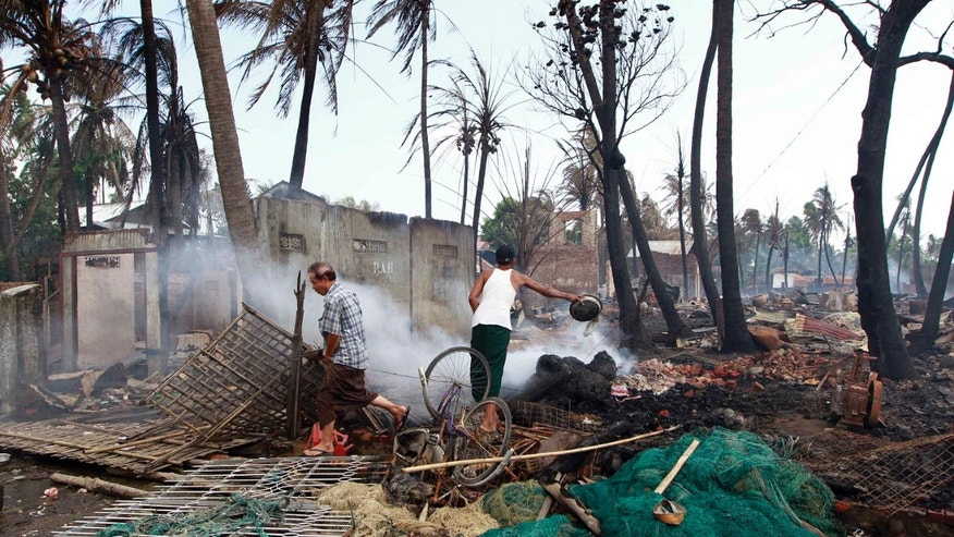 June 11, 2012: A man pours water on the debris of a burned house still smoldering as another man walks by in Sittwe, Myanmar.