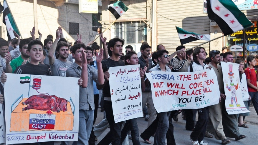 June 10, 2012: This citizen journalism image provided by Shaam News Network SNN, taken on Sunday, June 10, 2012 purports to show  Syrians chanting slogans and holding posters during a demonstration in Kfarnebel, Idlib province, northern Syria.
