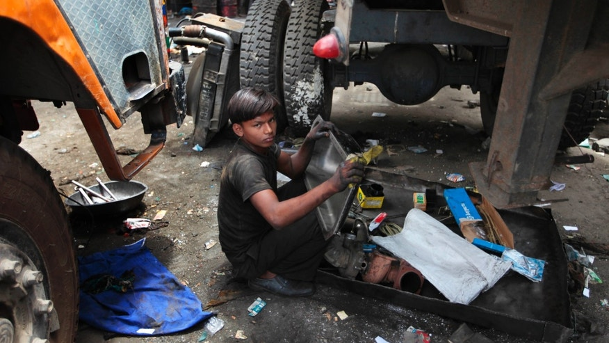 June 12, 2012: A young boy cleans parts of a truck on World Day Against Child Labor in New Delhi, India.