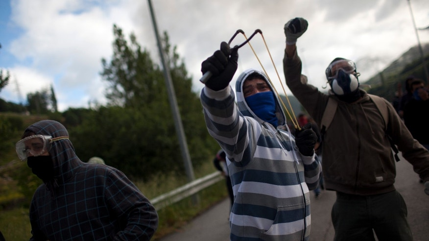 June 12, 2012: A miner uses a slingshot to throw stones against riot police officers, unseen, during clashes following a demonstration after blocking a motorway in Campomanes, Oviedo, Spain.