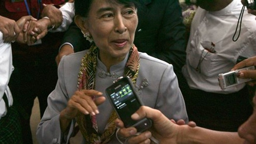 June 13, 2012: Myanmar opposition Leader Aung San Suu Kyi talks to reporters as she arrives at Yangon International airport in Yangon, Myanmar.