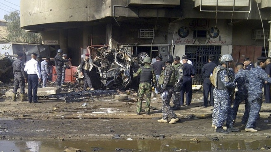 June 13, 2012: Iraqi security personnel inspect the site of a car bomb attack, which killed Shi'ite pilgrims who were making their way to a religious festival, in Baghdad.