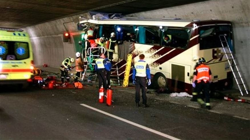 Rescuers and police work amid the wreckage of a tourist bus from Belgium at the accident site in a tunnel of the A9 highway near Sierre, western Switzerland, early Wednesday, March 14, 2012. A bus carrying Belgian students returning from a ski holiday crashed into a wall in a Swiss tunnel, killing 22 Belgian 12-year-olds and six adults, police said Wednesday.  (AP Photo/KANTONSPOLIZEI WALLIS/POLICE OF VALAIS, Handout)  MANDATORY CREDIT
