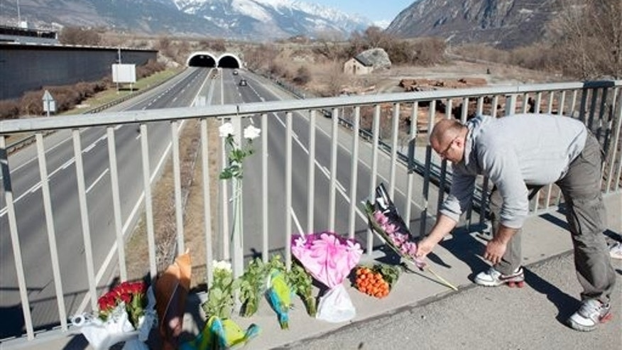 A man places a flower tribute on a bridge near the entrance of the tunnel where a tourist bus from Belgium crashed on the motorway A9, in Sierre, western Switzerland, Wednesday, March 14, 2012.  Twenty-eight people, including 22 children, returning to Belgium from a skiing holiday died in a bus accident inside the road tunnel in Sierre in the Swiss canton of Valais, Swiss police said Wednesday. (AP Photo/Keystone/Laurent Gillieron)