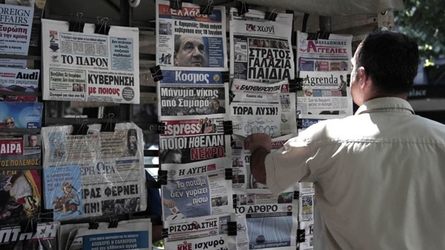 June 16, 2012: A man looks at the front pages of newspapers the day before general elections in Thessaloniki, Greece. Greeks vote for the second time in six weeks Sunday amid fears that the country could be forced out of the euro if they reject the strict austerity measures taken in return for billions of euros in rescue loans from other European countries and the International Monetary Fund.