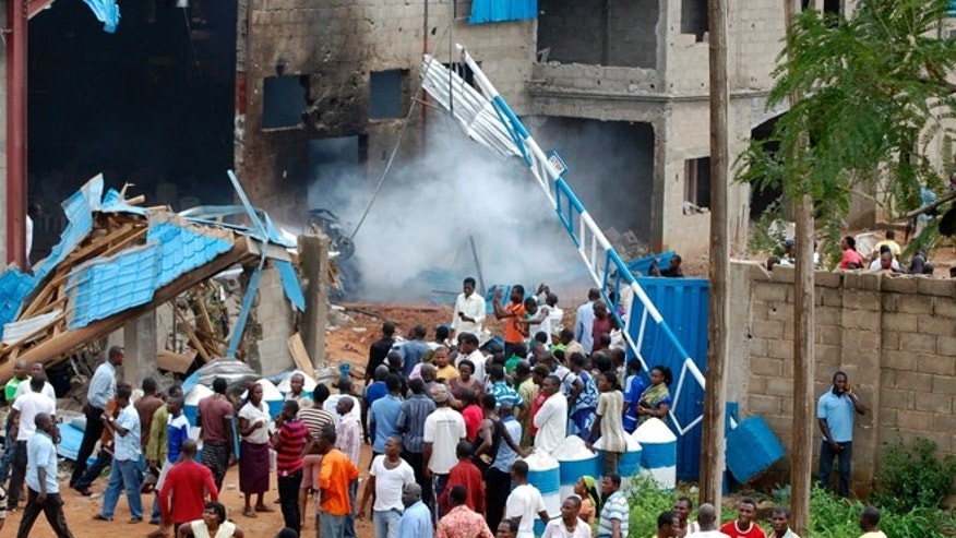 June 17, 2012: People gather outside a church following a blast in Kaduna, Nigeria.